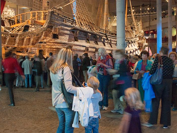 Besökare som tittar på Vasaskeppet i skeppshallen på Vasamuseet