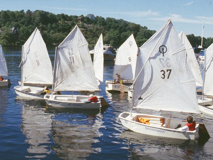 Barn seglar jollar i solsken