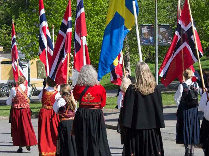 Flaggparad med norska och svenska flaggor och människor i folkdräkter